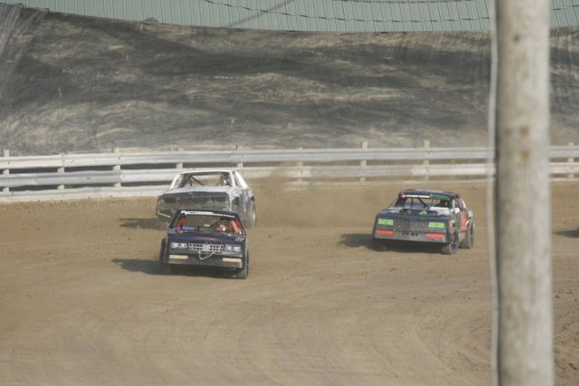 3 Race cars taking a turn at the Little Valley Speedway