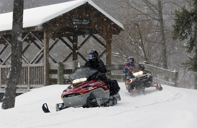 Snowmobiles exiting the Thomas L. Kelly Covered Bridge in Allegany State Park