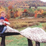 Photo of Kids on sculptures of mushrooms in a field at Griffis Sculpture Park