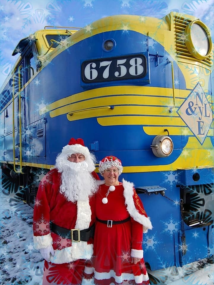 Santa and Mrs. Claus in front of the train