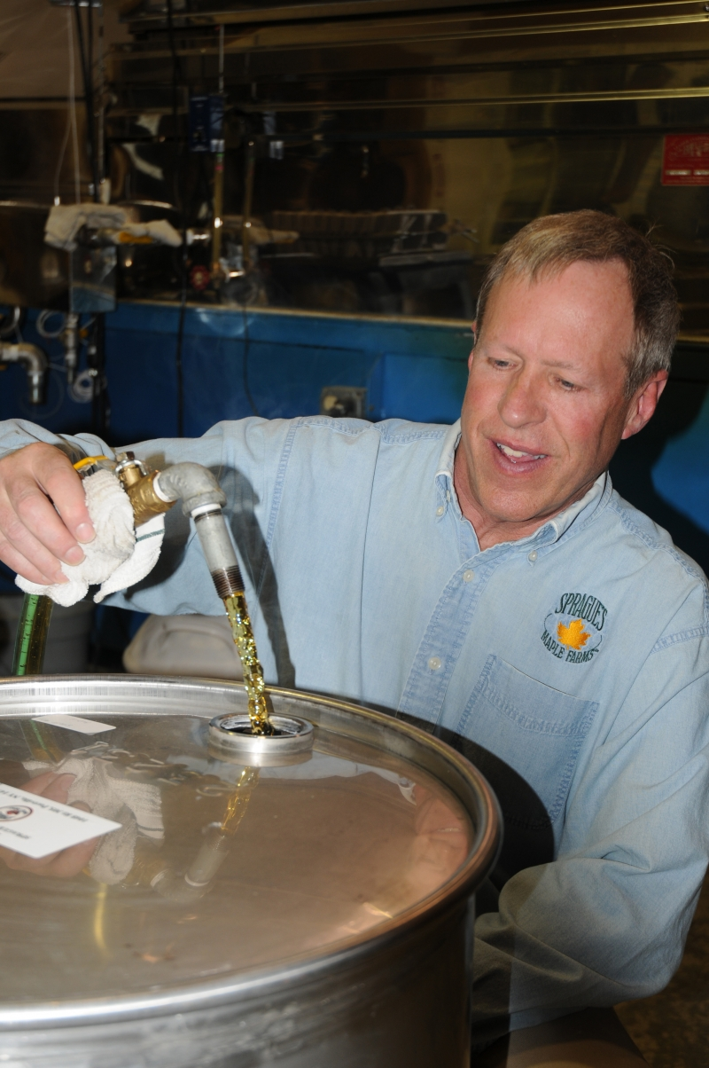 Photo of Randy Sprague filling a barrel with maple syrup