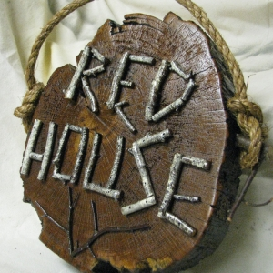 "A wooden piece with the words ""Red House"""