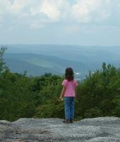 Little Girl standing on a huge rock overlooking the hills and valleys