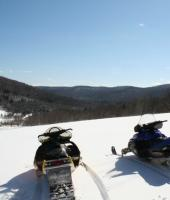 Two snowmobiles in the foreground with a Great View of the hillsides