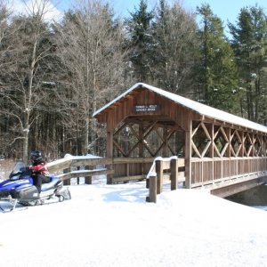 Snowmobiler exiting the Thomas Kelly Covered Bridge at Allegany State Park