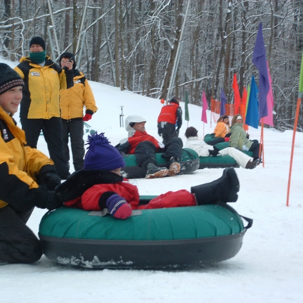 People getting ready to slide down the big hill at Holiday Valley Tubing Company