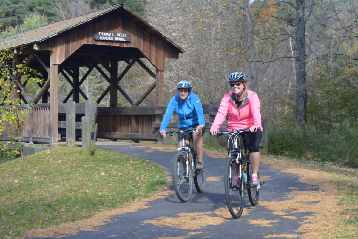Ladies riding bicycles on paved bike trail at Allegany State Park